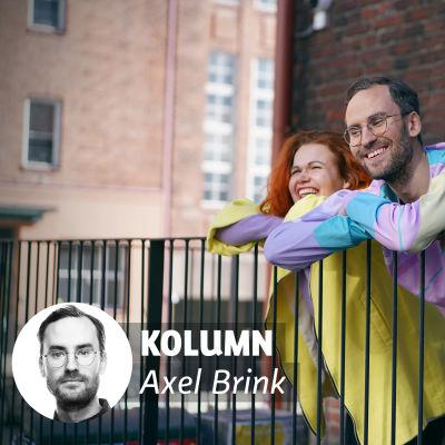 My och Axel befinner sig i en urban miljö, iklädda pastellfärgade kläder. My och Axel lutar mot ett metallräcke. De ser glada ut. Bakom dem syns en tegelvägg.