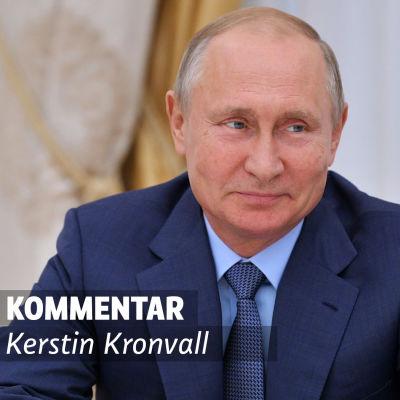 Vladimir Putin sitter och småler.
