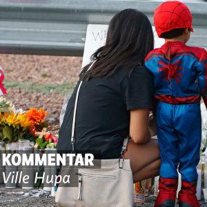 En kvinna och ett barn framför en minnesplats. Det finns mycket ljus och blommor. Text på bilden: Kommentar av Ville Hupa.