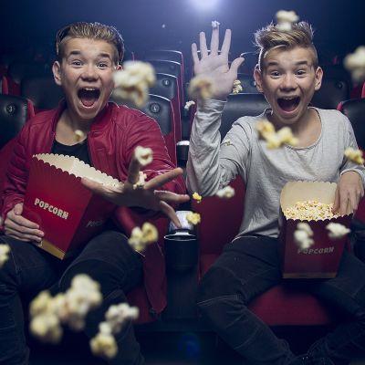 Marcus ja Martinus istuvat elokuvateatterissa, nauravat ja heittävät popcornia kohti kameraa.