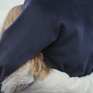 Man som kramar sin dotter