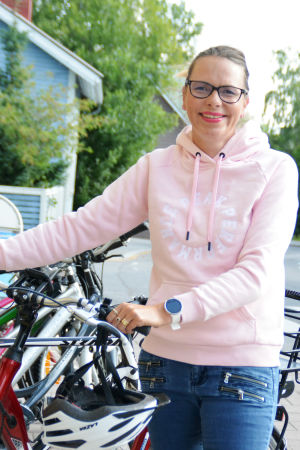 Hanna-Maria Grandell står vid sin cykel. En pojke på cykel cyklar förbi.