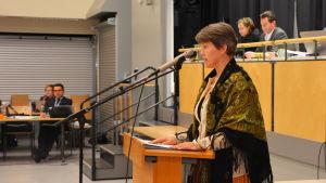 En kvinna står framför ett podium och talar i mikrofon.