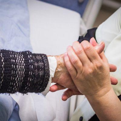 Hoitaja pitelee vanhuksen kättä.