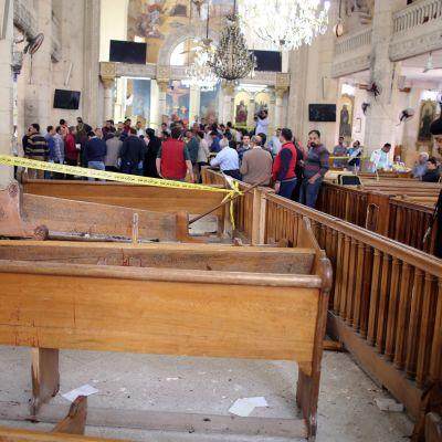 Kirkossa mustiin pukeutunut pappi katsoo hajonneita kirkon penkkejä, joiden yllä kulkee eristysnauhaa. Taustalla väkijoukko.