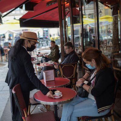 Tarjoilija palvelee asiakasta pariisilaisessa kahvilassa 19. toukokuuta.
