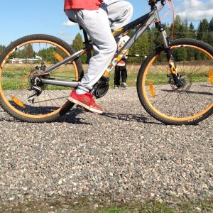Barn som cyklar på grusväg