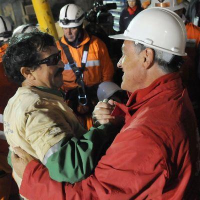 Chilen presidentti Sebastian Pinera halaa pelastettua kaivosmiestä Mario Sepulvedaa Chilessä, 13. lokakuuta 2010.