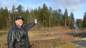 En man i svart läderjacka och keps står invid en väg. Han ser in i kameran och pekar med hela armen mot en punkt någonstans ovanför trädtopparna som syns bakom honom.