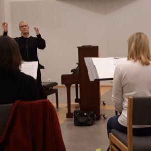 Kuoronjohtaja Sanna Kuusisto johtaa harjoitusta.