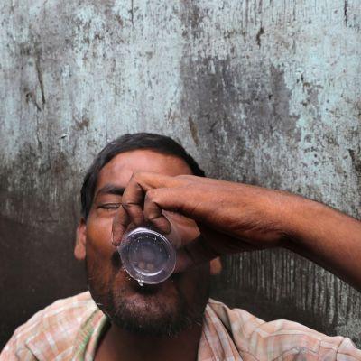 Intialainen mies juo kotipolttoista alkoholia Kalkutassa vuonna 2013.