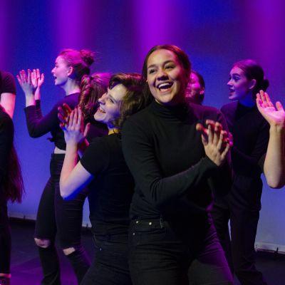 Ungdomsteatern Nya Tadams medlemmar dansar på en teaterscen.