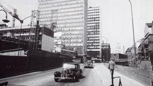 Ett svartvitt fotografi, bilar kör förbi platsen där Hötorgsskraporna i Stockholm håller på att byggas år 1959.