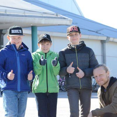 Adam Nässlin, Nico Källberg och Hugo Sundsten ger tummen upp för Skolmusik 2017. Läraren Tobias Tåg sitter på huk bredbid pojkarna.
