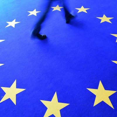 Mies kävelee matolla jossa on EU-lipun tähdet.