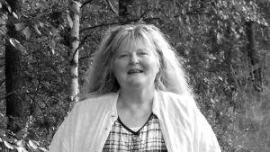 Runoilija Kaarina Valoaalto kulkee koivujen reunustamaa tietä.