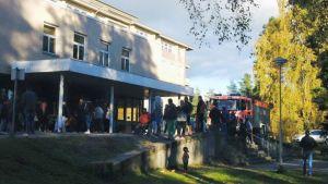 Människor står utanför en byggnad. En brandbil är parkerad bakom dem.