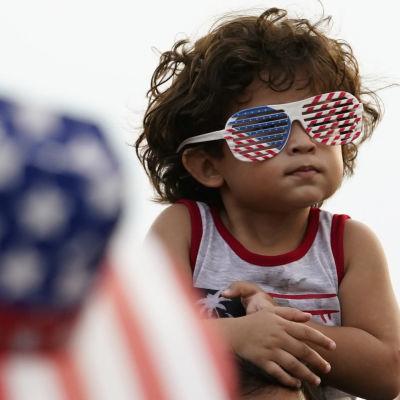 En liten pojke har glasögon på sig i USA:s flaggas färger.