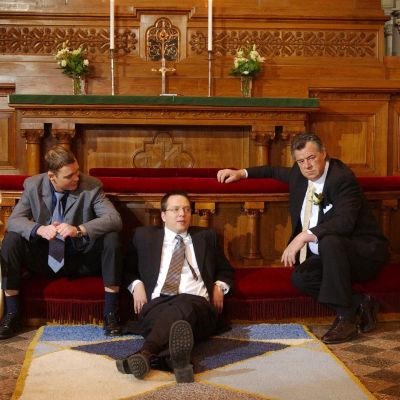 Kotikadun Tuija, Teemu, Janne, Mauri ja Onni kirkon alttarissa. He istuvat ja nojailevat rennosti.