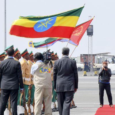 Kuvassa kaksi liehuvaa lippua, sotilaita, valokuvaaja ja kaksi kumartavaa miestä punaisella matolla.