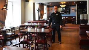 En man klädd i svart står mitt i en tom restaurang. Han ler och håller handen på en stolsrygg.