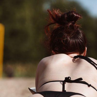 Nainen ottaa vatsallaan aurinkoa.