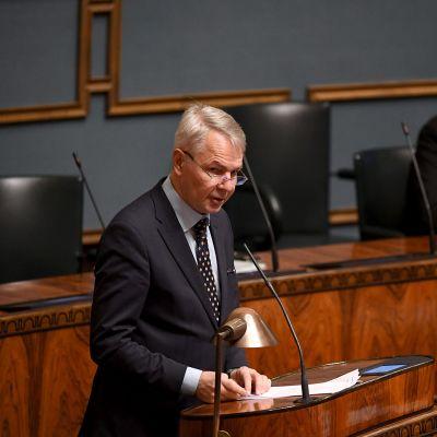 Ulkoministeri Pekka Haavisto (vihr.) puhuu ja taustalla istuu puolustusministeri Antti Kaikkonen (kesk.) eduskunnan täysistunnossa Helsingissä 30. marraskuuta 2020