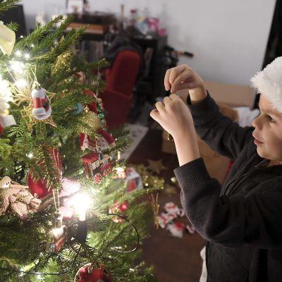 7-vuotias poika koristelee joulukuusta.