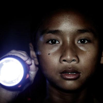 Närbild på en liten pojke som lyser med en flicklampa.