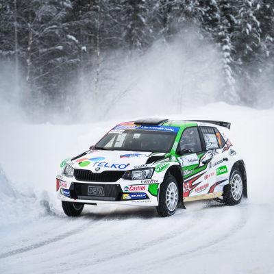 Rallybil kommer med hög hastighet på vinterväg.