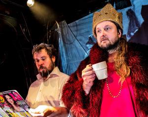 Antti Mankosen näyttelemä Jussi lukee Anna-lehteä. Vieressä seisoo kahvikuppi kädessään ja kruunu päässään Pekko Käpin näyttelemä kuningatar Kristiina.