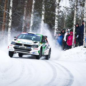 En rallybil susar fram på en vintrig skogsväg.