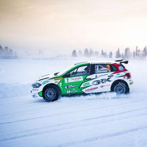 En rallybil susar fram på en vintrig väg.