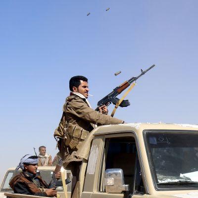 Kapinallinen ampuu rynnäkkökiväärillä ilmaan.