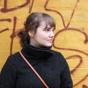 en kvinna framför en gul vägg med röd grafitti på iklädd svart jacka