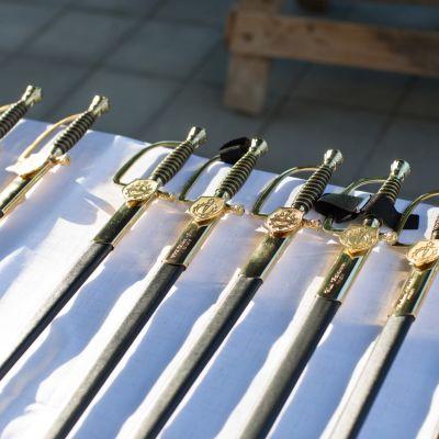 Auringossa kiiltäviä miekkoja rivissä valkoisen pöytäliinan päällä.