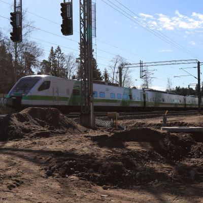 Tåg ilar förbi ställe där banarbeten pågår.