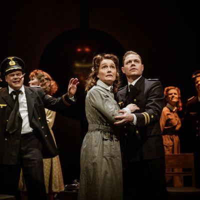 En kvinna i överrock och en man i uniform håller om varandra och ser oroade uppåt. I bakgrunden står en grupp människor.