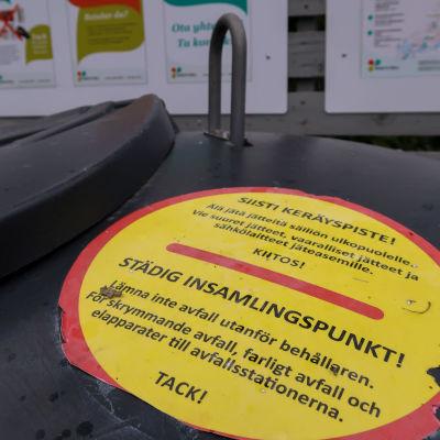 Bild av en påklistrad skylt på en avfallscontainer som uppmanar att inte lämna avfall utanför behållaren.