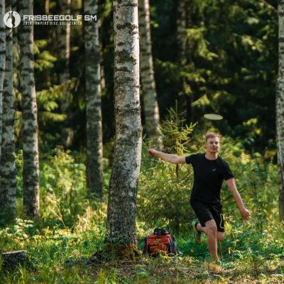 En svartklädd man springer i skogen och ler. En frisbee flyger ovanför hans huvud.