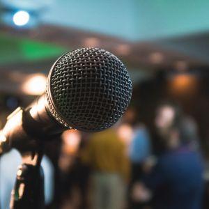 mikrofoni, taustalla yleisöä