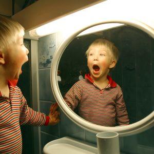En pojke ser sig själv i spegeln