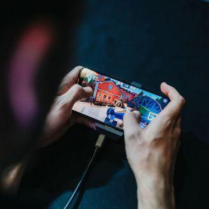 Mies pelaa mobiilipeliä