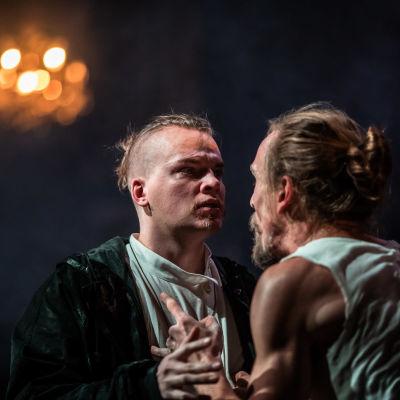 Miro Lopperi (Ivan Karamazov) ja Juho Uusitalo (Aleksei Karamazov) seisovat vastakkain lähellä toisiaan, Ivan selittää, Aleksei kuuntelee.