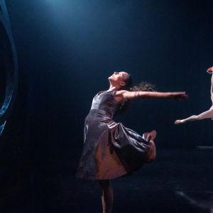 En kvinnlig dansare i silverskiftande klänning på en mörk scen.