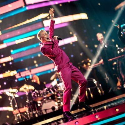 Antti Tuisku esiintyy värikäs puku yllään SuomiLOVE-lavalla.