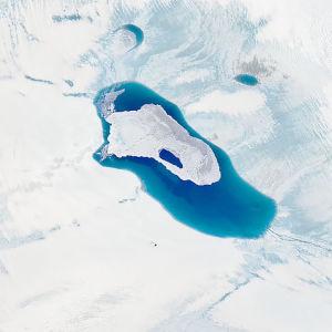 En satelitbild på grönlandsisen. I mitten syns en större vattenmassa där isen smält och bildat något som liknar en sjö.