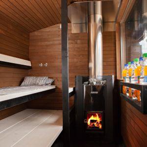 Saunabussin sauna. Puulämmitteisessä kiukaassa on tuli.