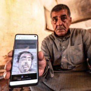 En sorgsen äldre man i gråbrun skjorta håller fram en mobil med en bild på en yngre man.