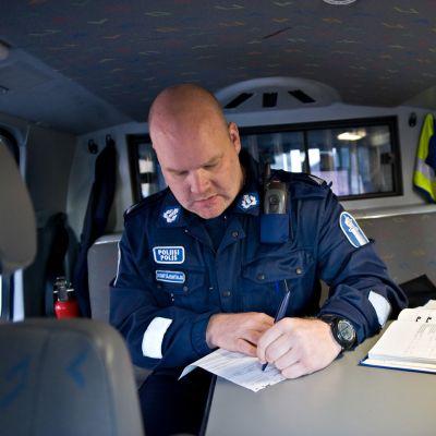 Poliisi istuu poliisiautossa ja kirjoittaa. HUOM: Kertakäyttöoikeus.